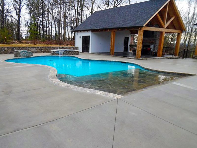Law Pools & Patio walk in beach pool with spill over spa and diving rock