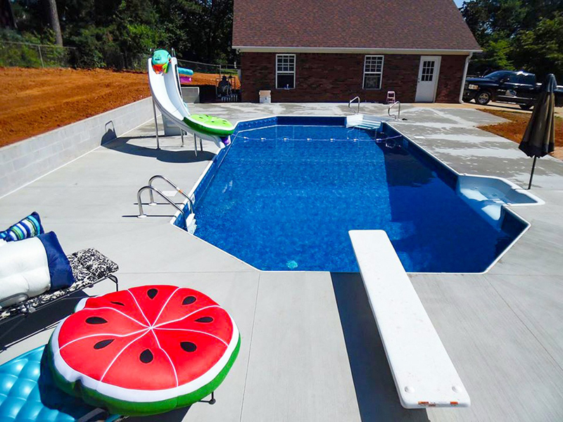 Law Pools & Patio grecian diving pool with slide and seating area