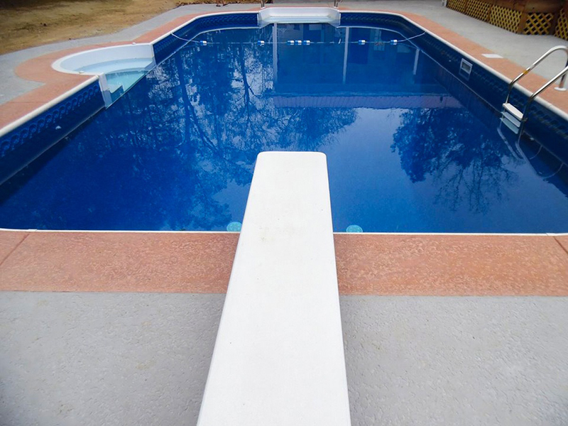 Law Pools & Patio rectangle pool with diving board and seating area