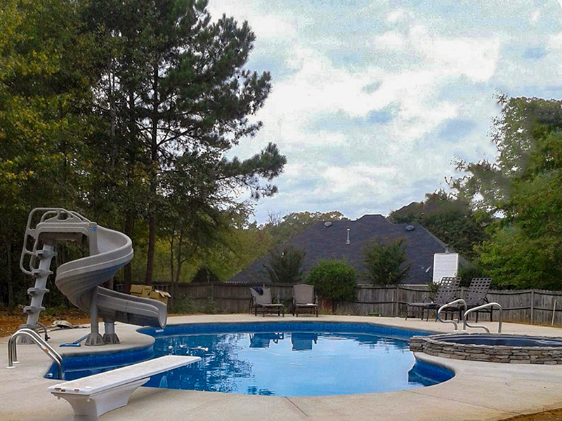 Law Pools & Patio pool with spiral slide, diving board, and spillover spa