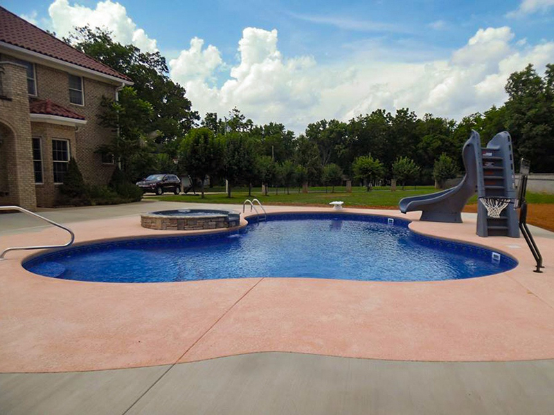 Law Pools & Patio custom lagoon pool with slide, basketball hoop, diving board, and spa
